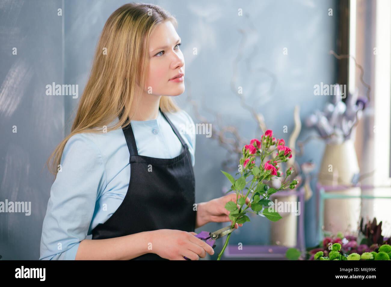 florist thinking about arranging flowers, making up floral wonderland - Stock Image