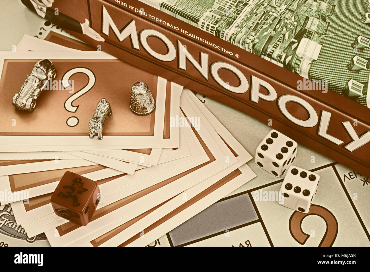 Tambov, Russian Federation - January 26, 2018 Monopoly Board Game box, Chance cards, tokens, dices on the gameboard. - Stock Image