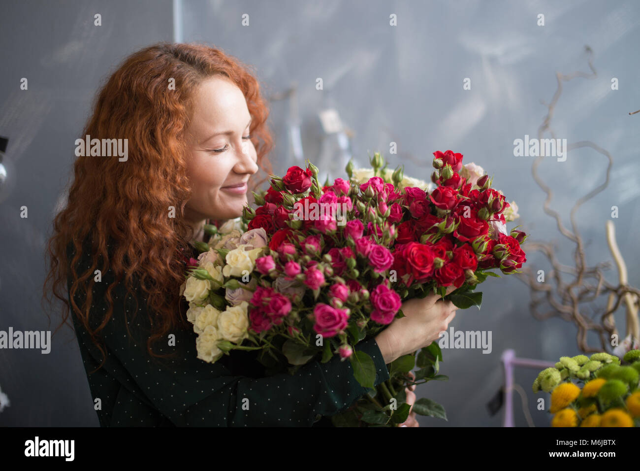Female florist smelling flower bouquet in the flower shop Stock Photo