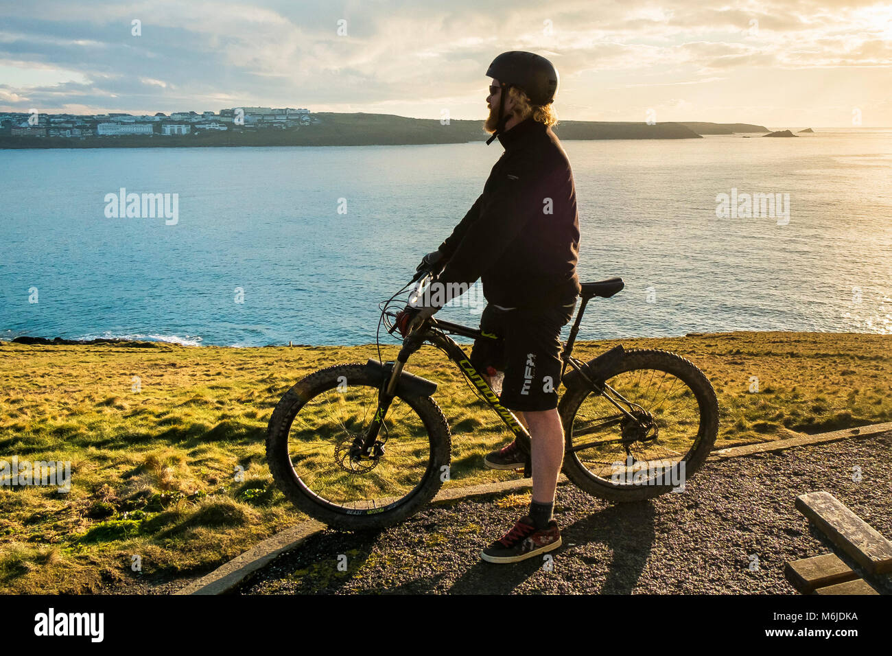 A mountain biker at the top of Towan Head in Newquay Cornwall. - Stock Image