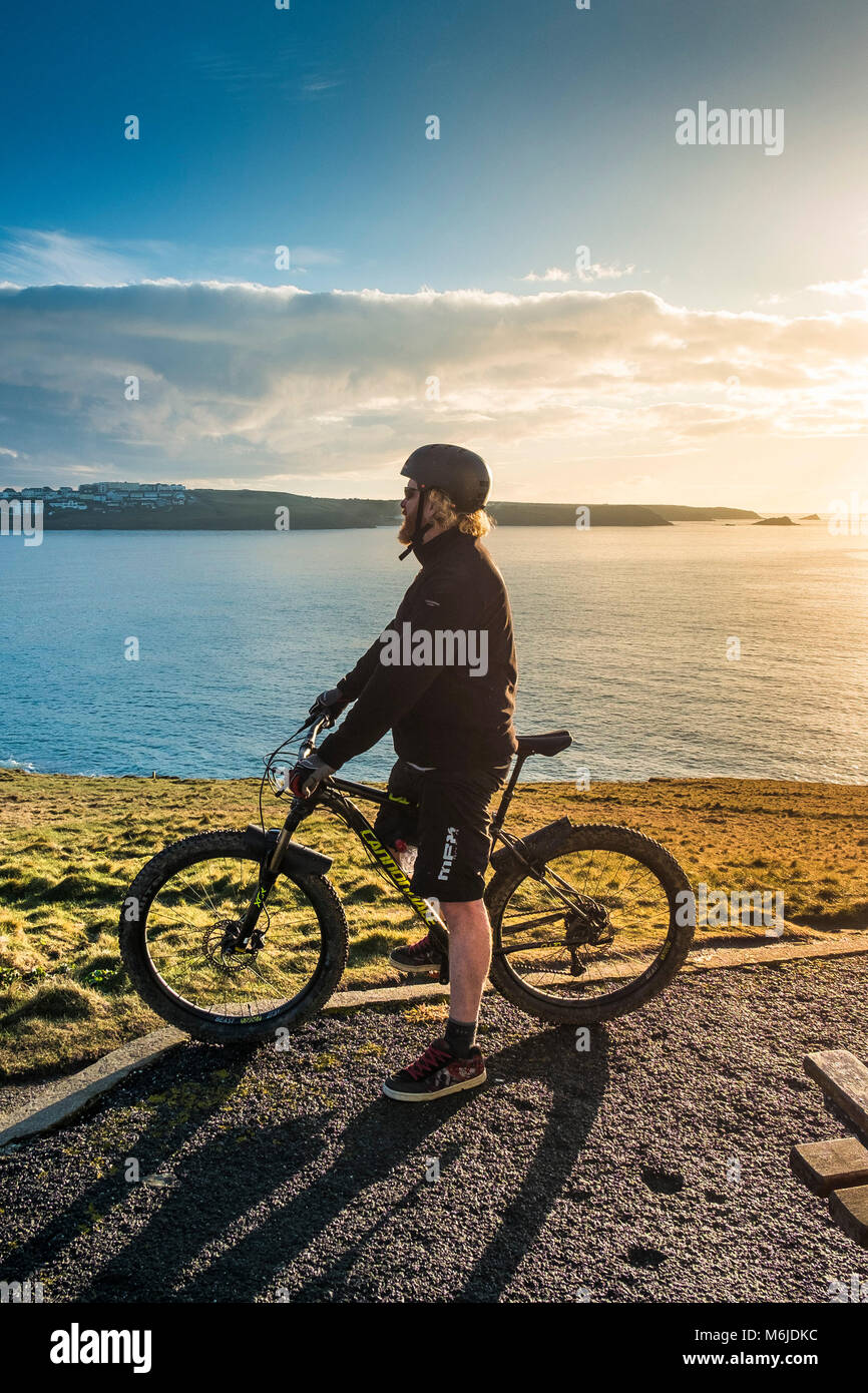 A mountain biker standing on the top of Towan Head in Newquay Cornwall. - Stock Image