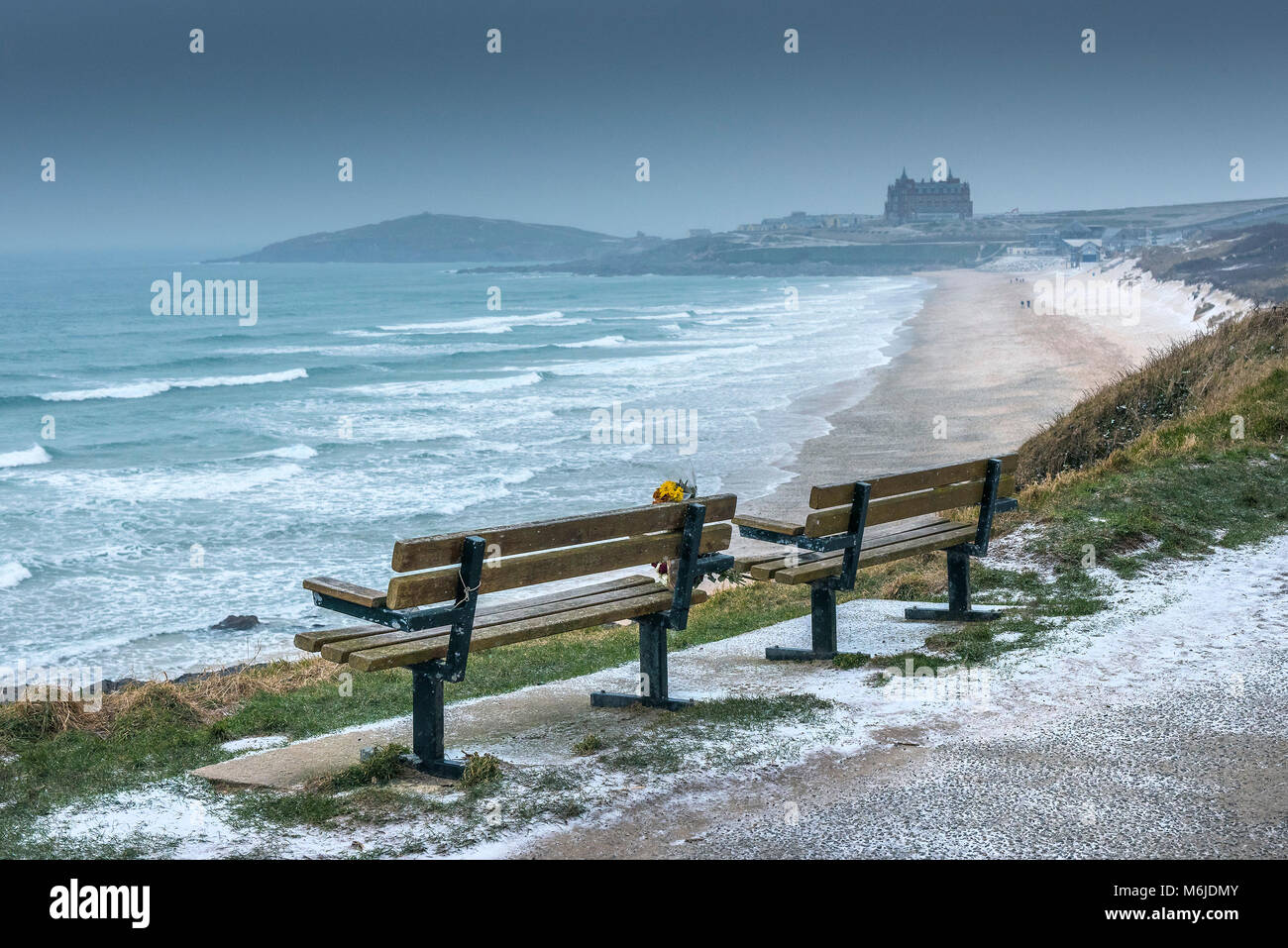 Two empty benches overlooking a cold Fistral Beach wintry weather conditions in Newquay Cornwall. - Stock Image