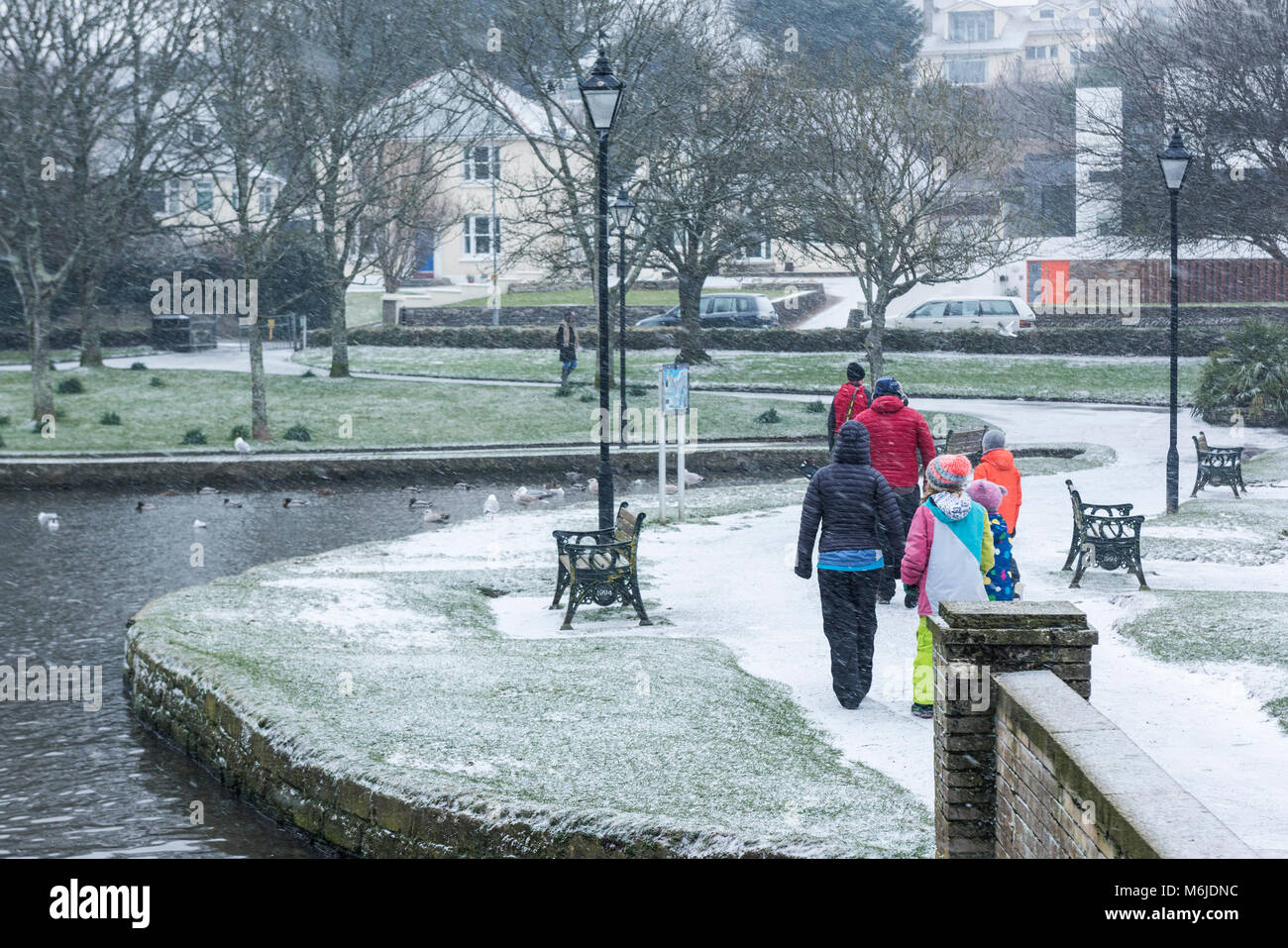 A family wearing brightly coloured clothes during a snow fall in Trenance Gardens in Newquay Cornwall. - Stock Image