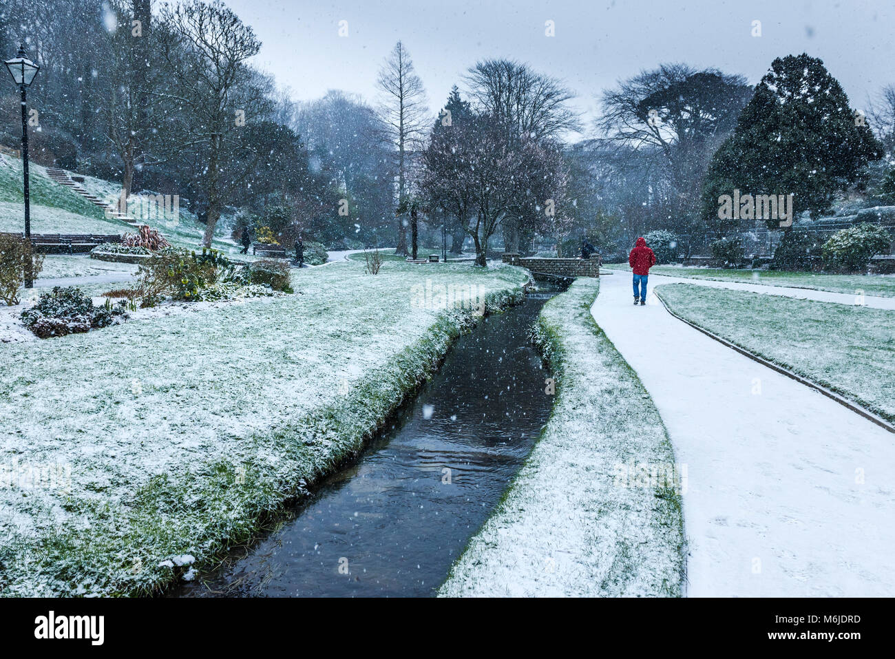 People walking through heavy snowfall in Trenance Gardens in Newquay Cornwall. - Stock Image