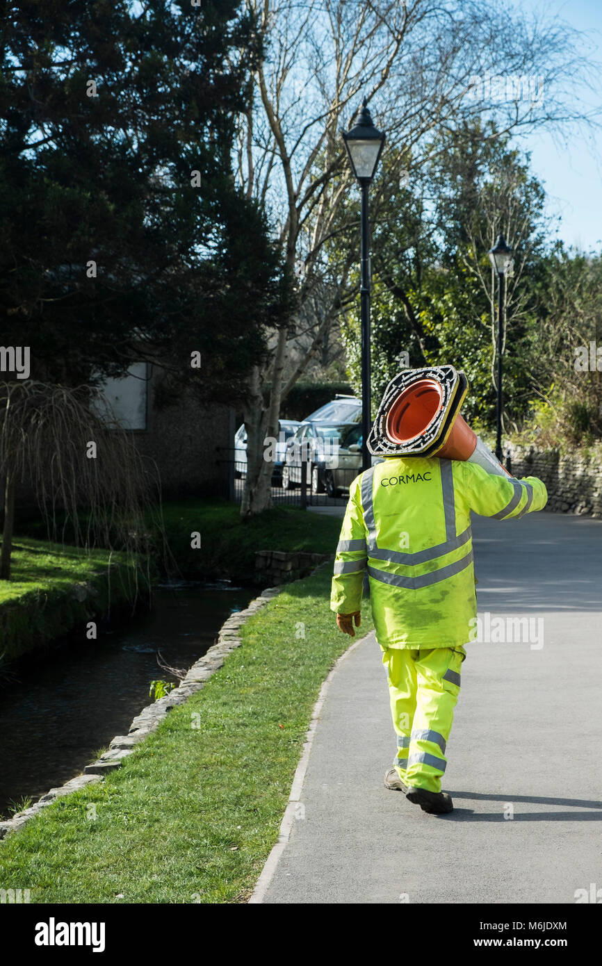 A Cormac worker carrying traffic cones in Trenance Gardens Newquay Cornwall. - Stock Image