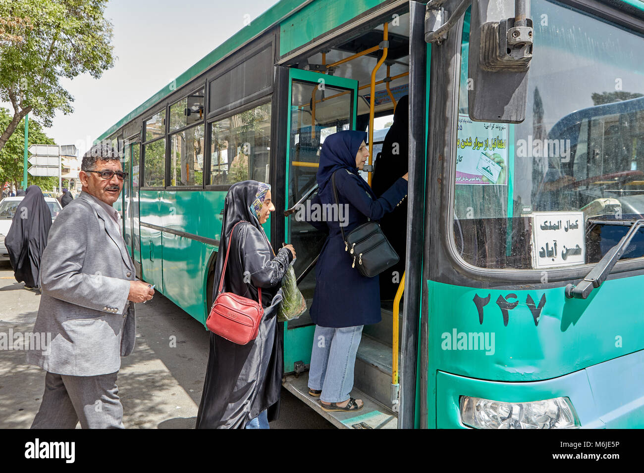 Kashan, Iran - April 27, 2017: Passengers enter the municipal bus at a public transport stop. Stock Photo