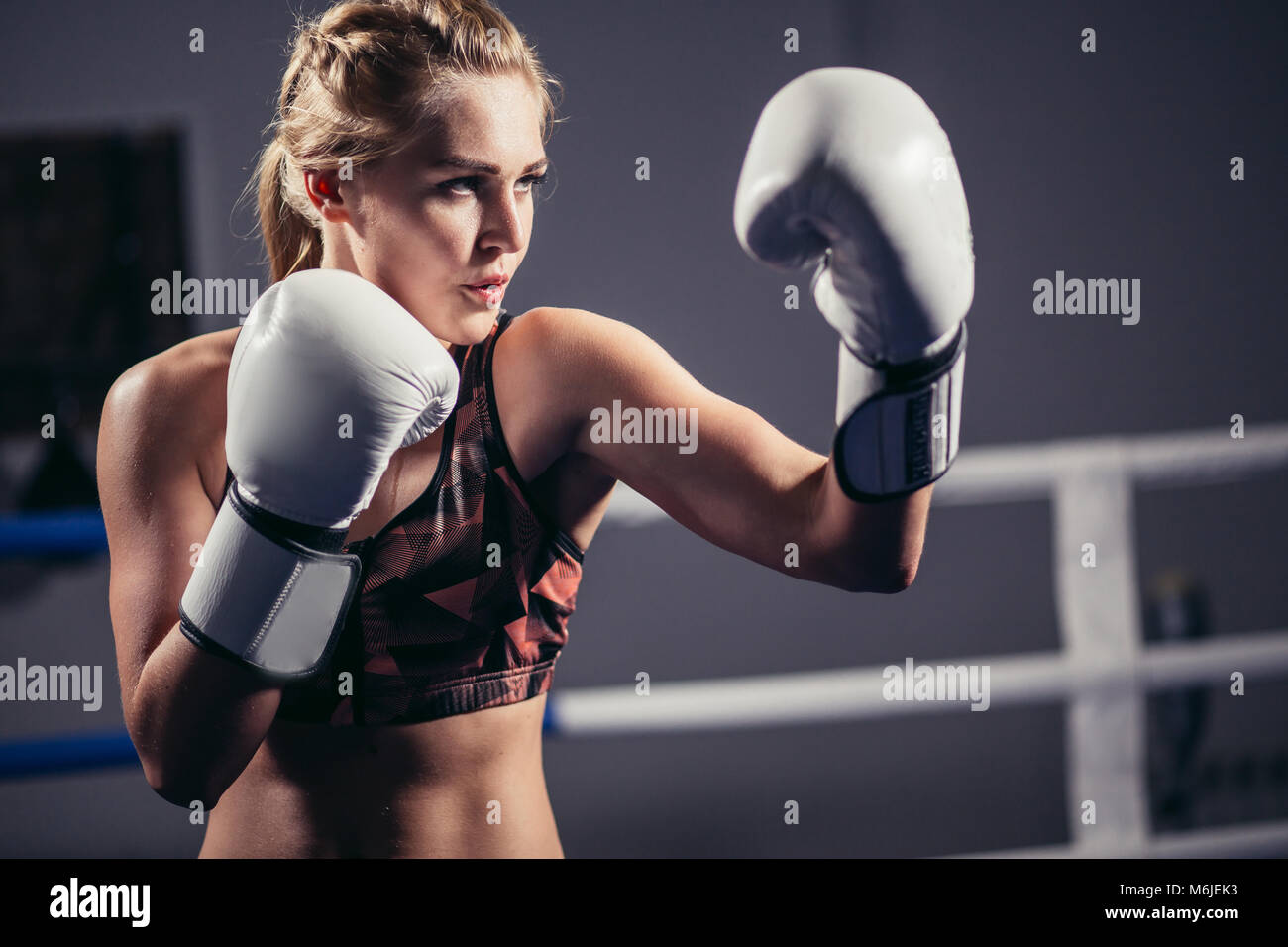 16360480eaff Female Boxer wearing gloves posing in boxing studio Stock Photo ...