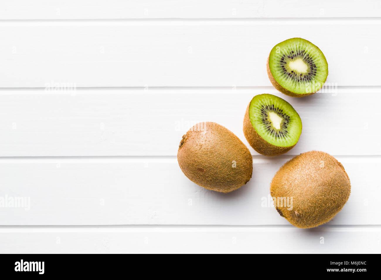 Halved kiwi fruit on white table. - Stock Image