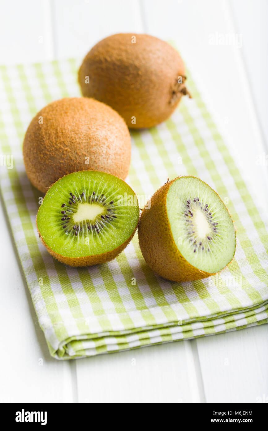 Halved kiwi fruit on checkered napkin. - Stock Image