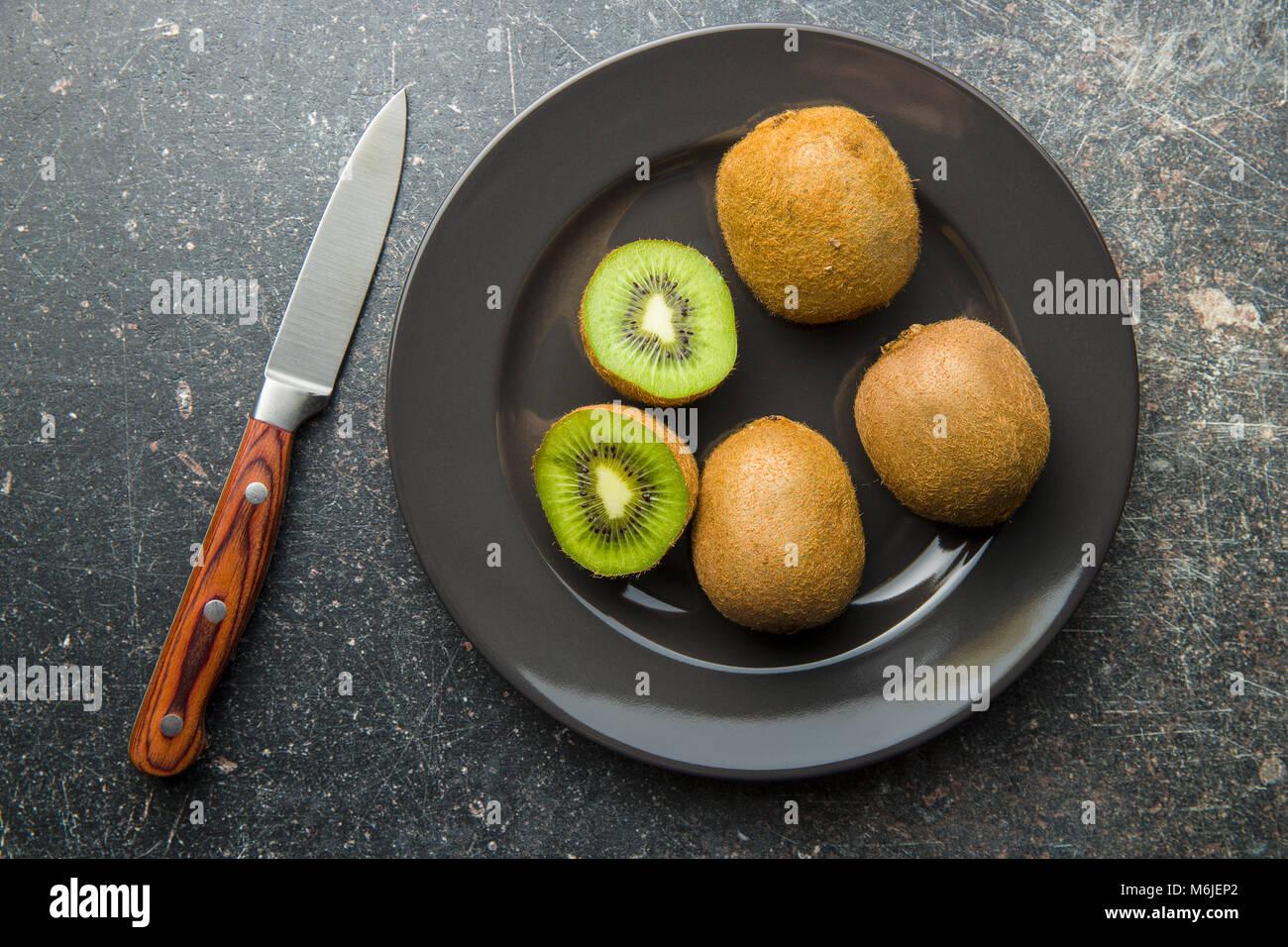 Halved kiwi fruit on plate. - Stock Image
