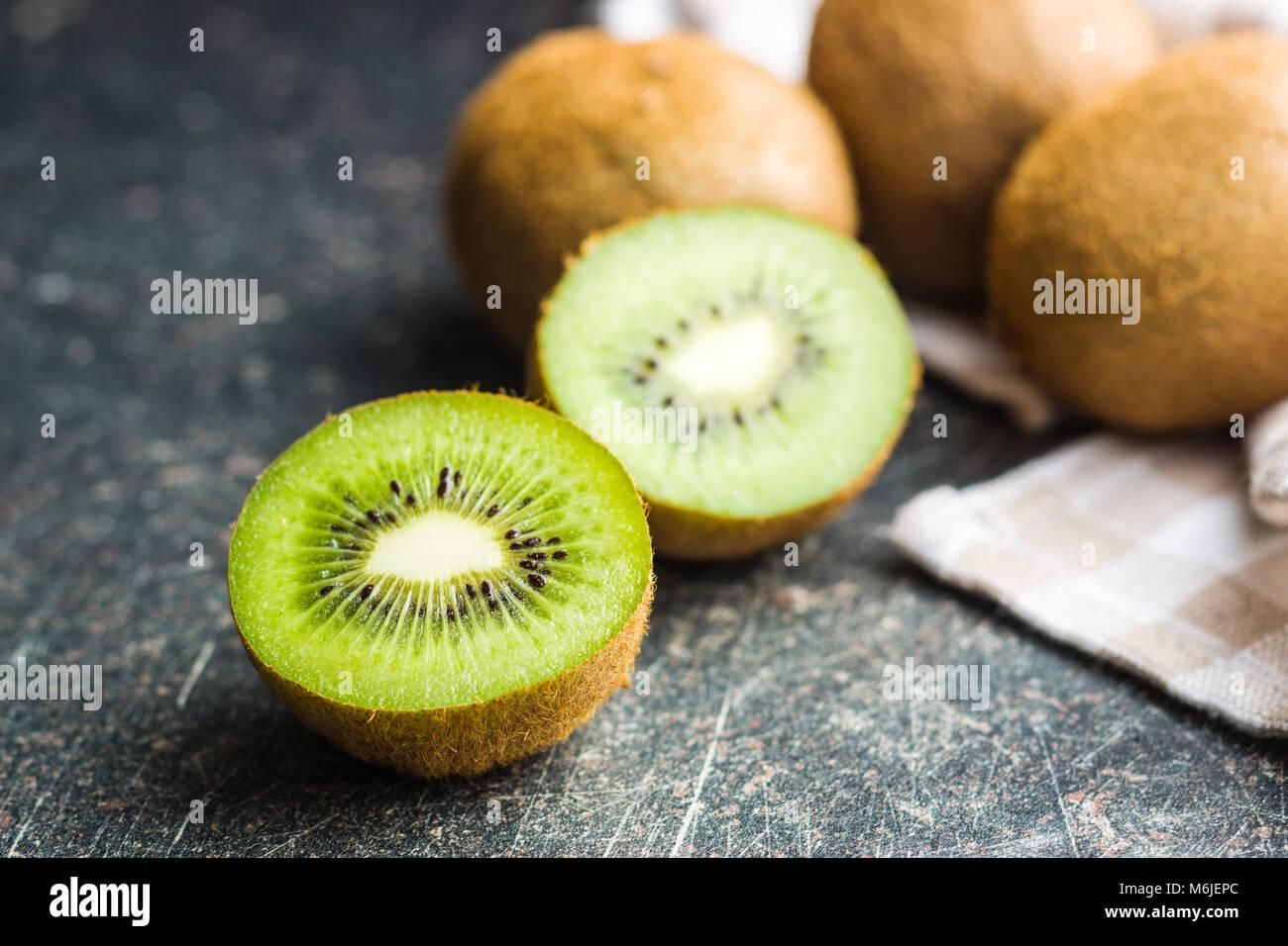 Halved kiwi fruit on old kitchen table. - Stock Image