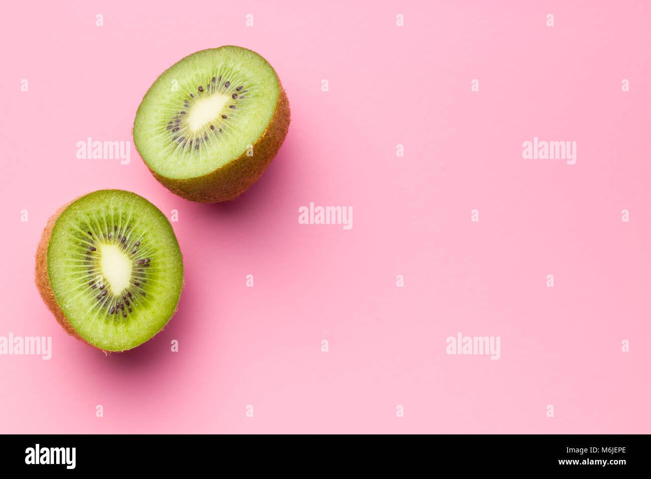 Halved kiwi fruit on pink background. - Stock Image