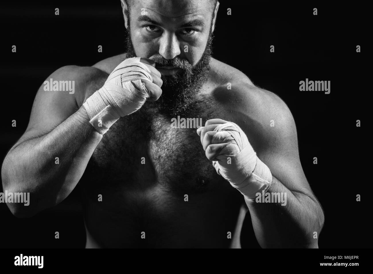 man boxing workout on ring. Caucasian male boxer in black gloves - Stock Image
