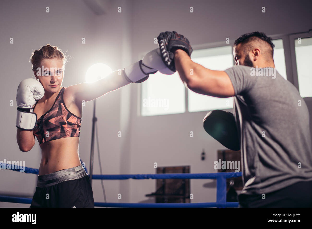 Boxing girl training on boxing mitts held by a master boxer - Stock Image