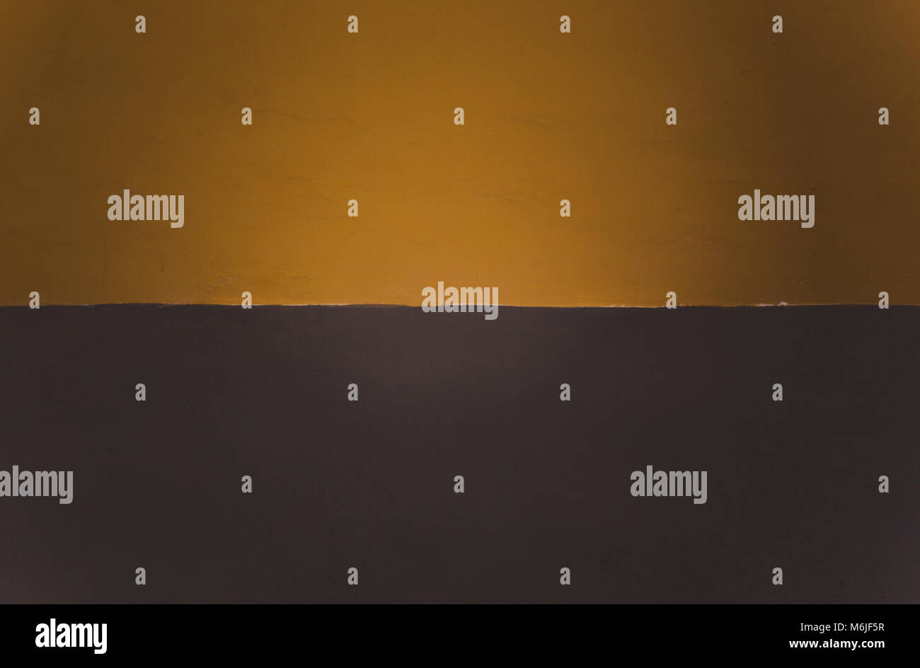 Two-toned split mustard yellow/orange and brown painted background with space for copy - Stock Image