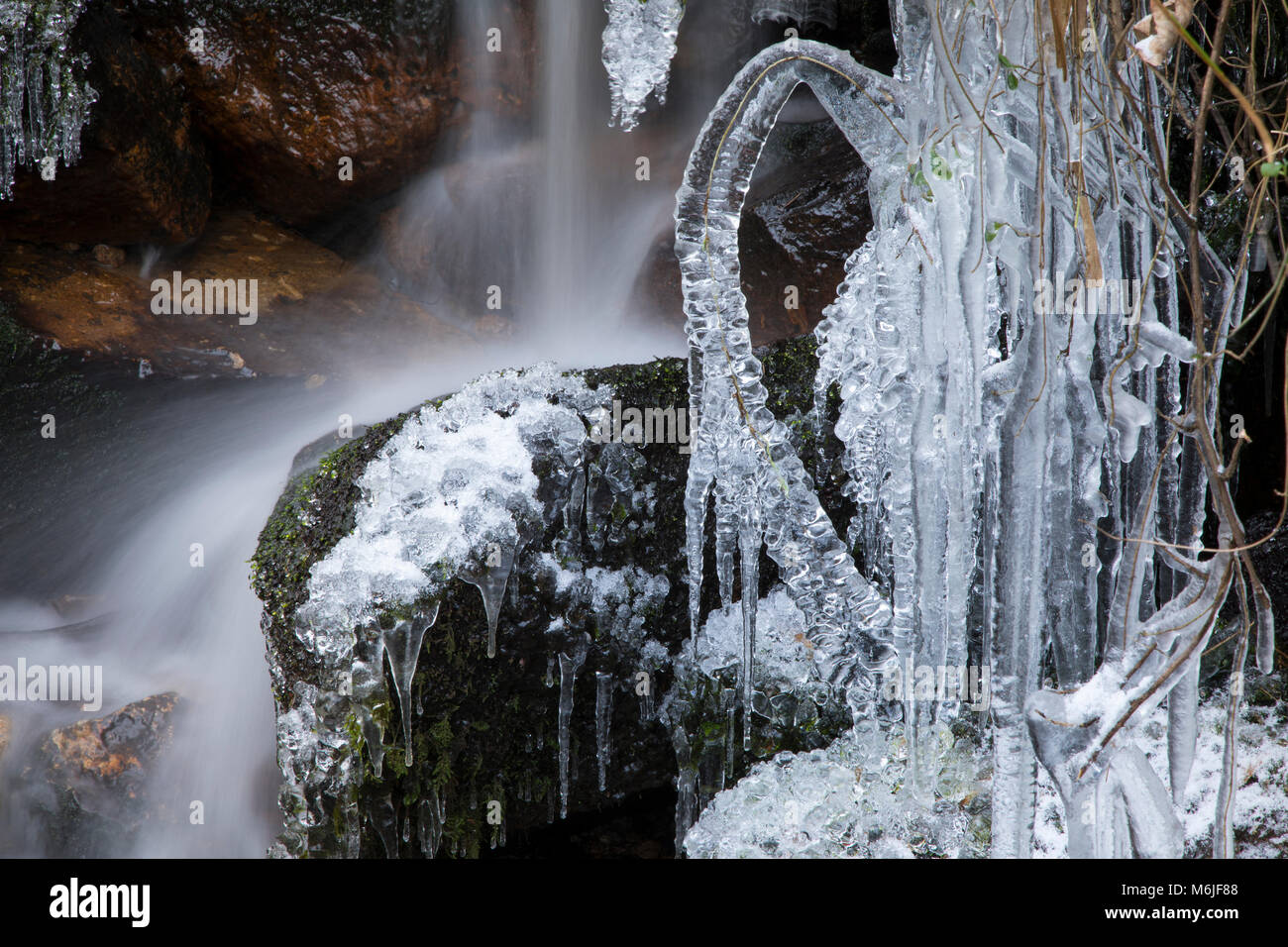 Long Exposure of water flowing down a waterfall with icicles frozen in the foreground, River Erme, Dartmoor, Devon. - Stock Image