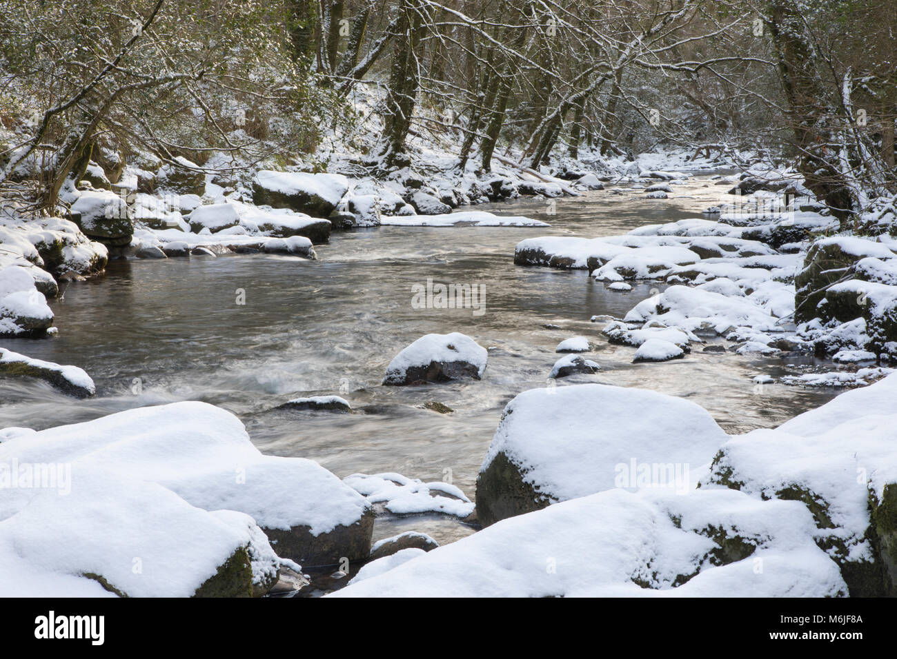 Long Exposure of water flowing down a stream surrounded by snow, River Erme, Dartmoor, Devon. - Stock Image