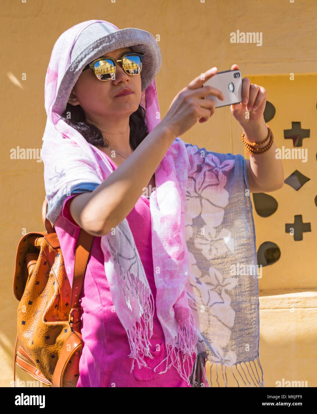 Visitor taking photos with reflections in sunglasses at Shwezigon Pagoda, Nyaung U, Bagan, Myanmar (Burma), Asia Stock Photo