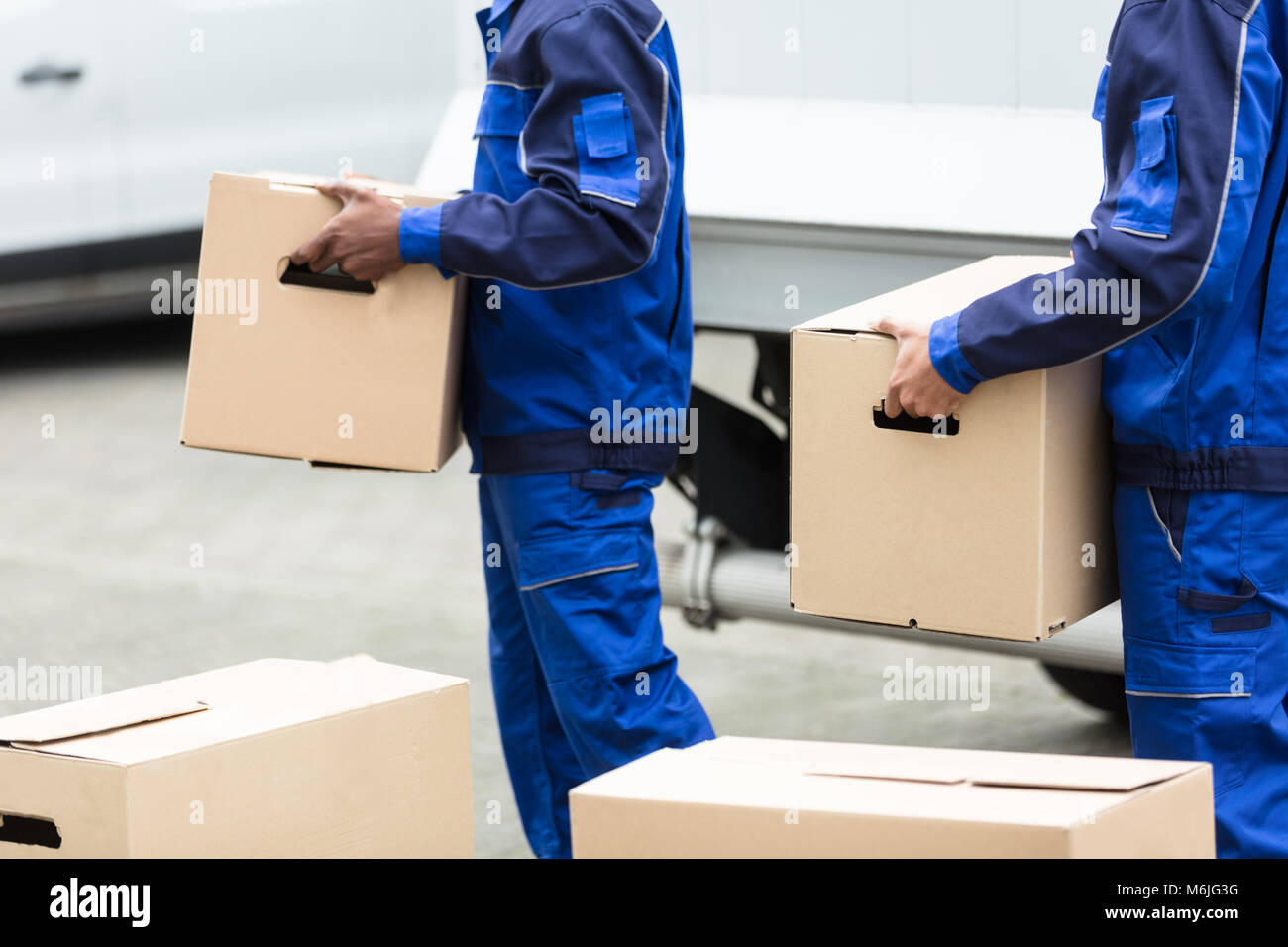 Close-up Of Two Delivery Men Holding The Cardboard Boxes - Stock Image