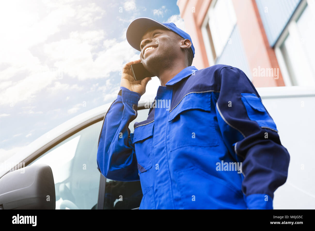 Low Angle View Of Happy Delivery Young Man Standing Near Van Talking On Cellphone - Stock Image