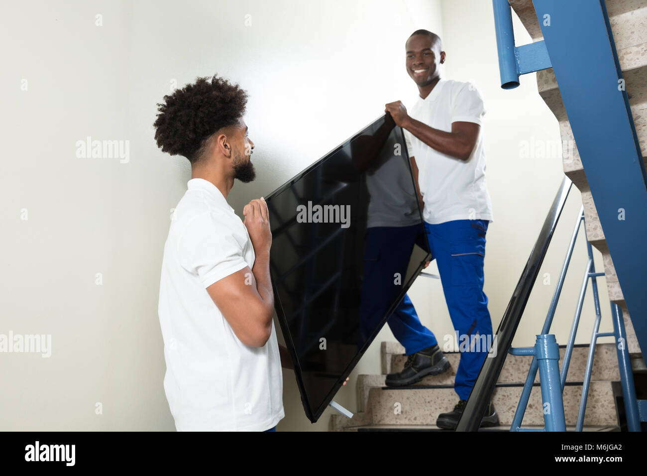 Close-up Of Two Male Young Movers Carrying Television While Climbing Steps At Home - Stock Image