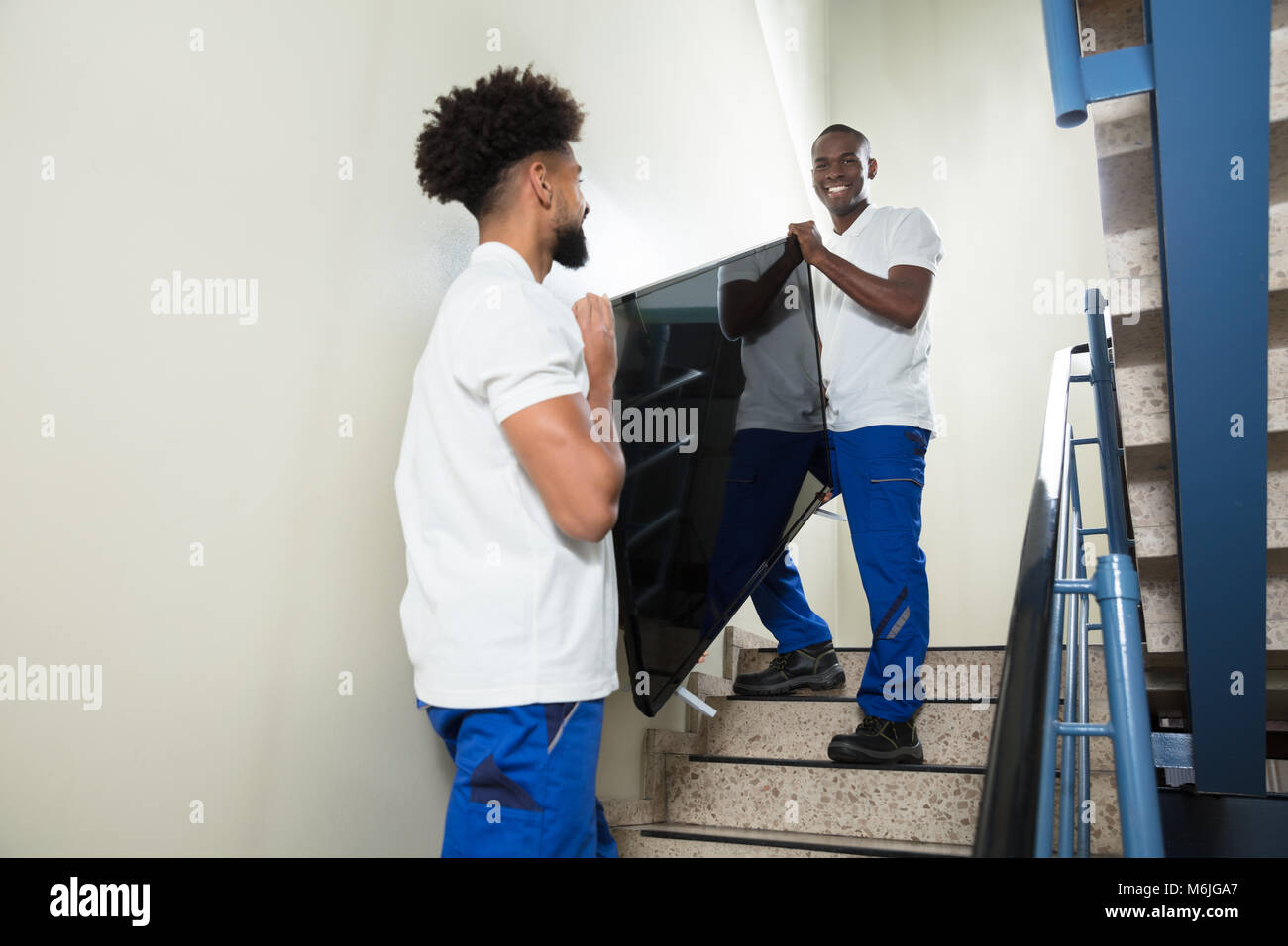 Close-up Of Two Male Young Movers Carrying Television While Climbing Steps At Home Stock Photo