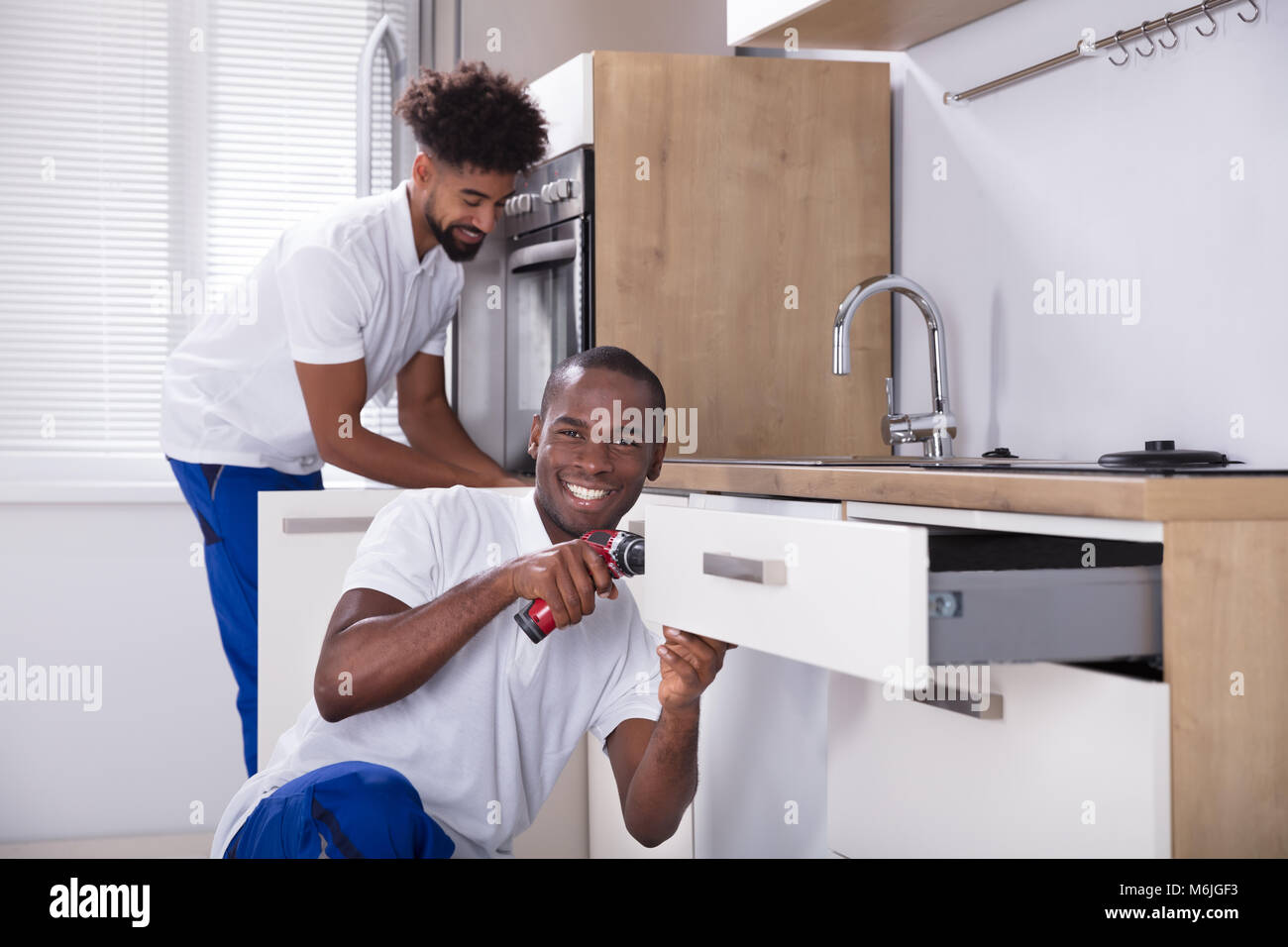 Rear View Of Two Happy Young Handy Men Fixing The Wooden Cabinet In The Kitchen Stock Photo