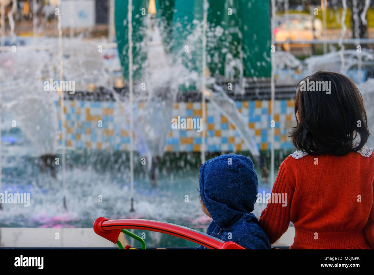 Two asian small girls standing in Shopping Trolley watching fountain in front of Mushrif Mall - Stock Image