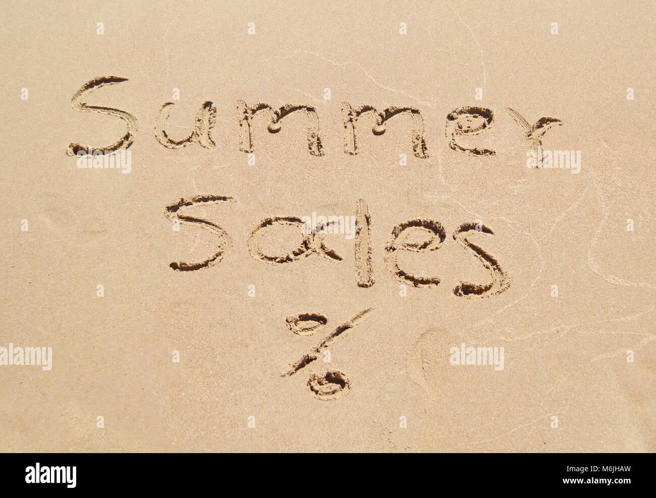 summer sales written on sand - seasonal discount shopping - Stock Image