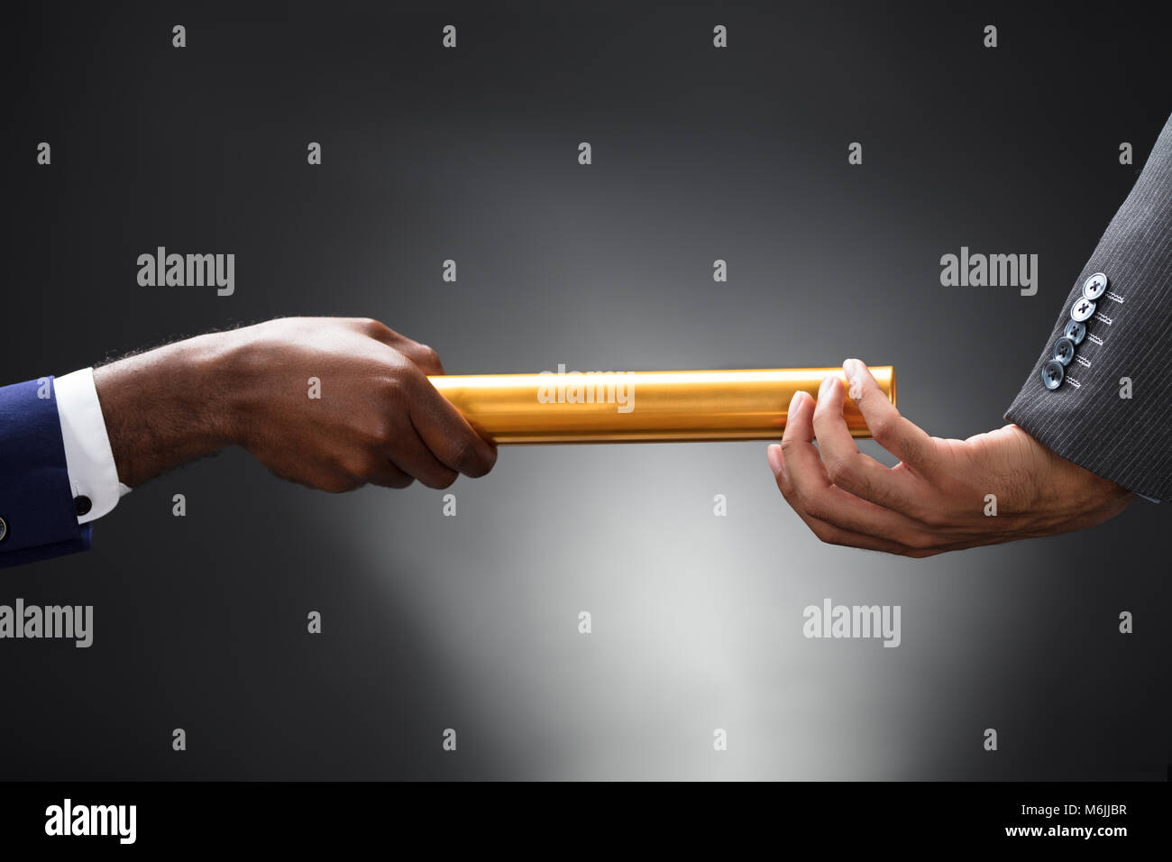 Man Passing The Golden Baton To His Partner On Gray Background - Stock Image