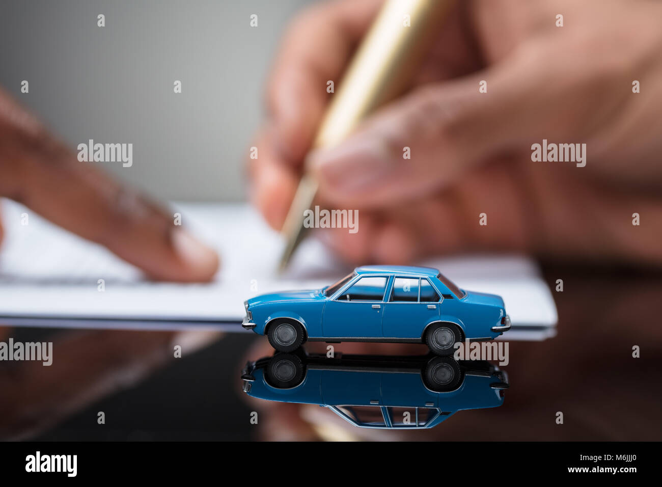 A Person\'s Hand Signing Car Loan Agreement Contract With Car Toy On ...
