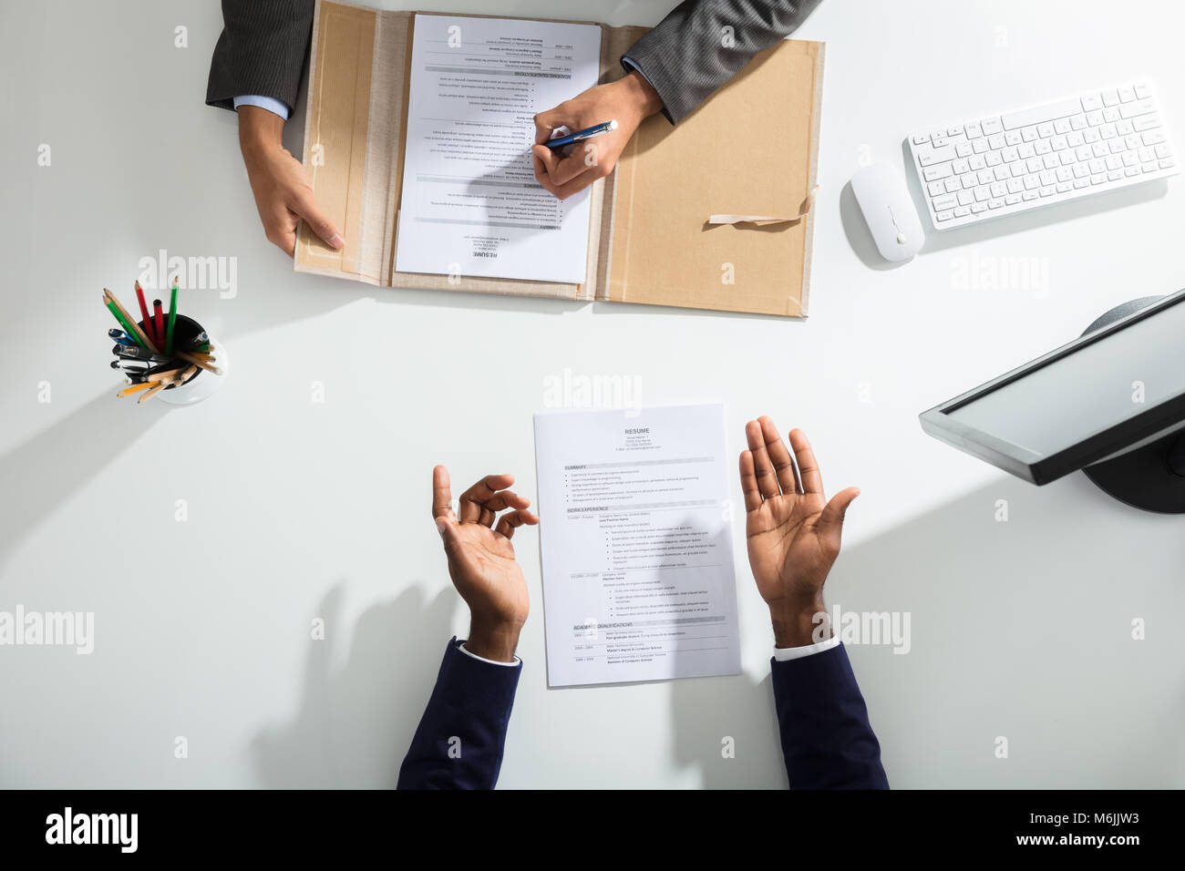 Elevated View Of Businessperson And Candidates Hand With Resume On White Desk - Stock Image