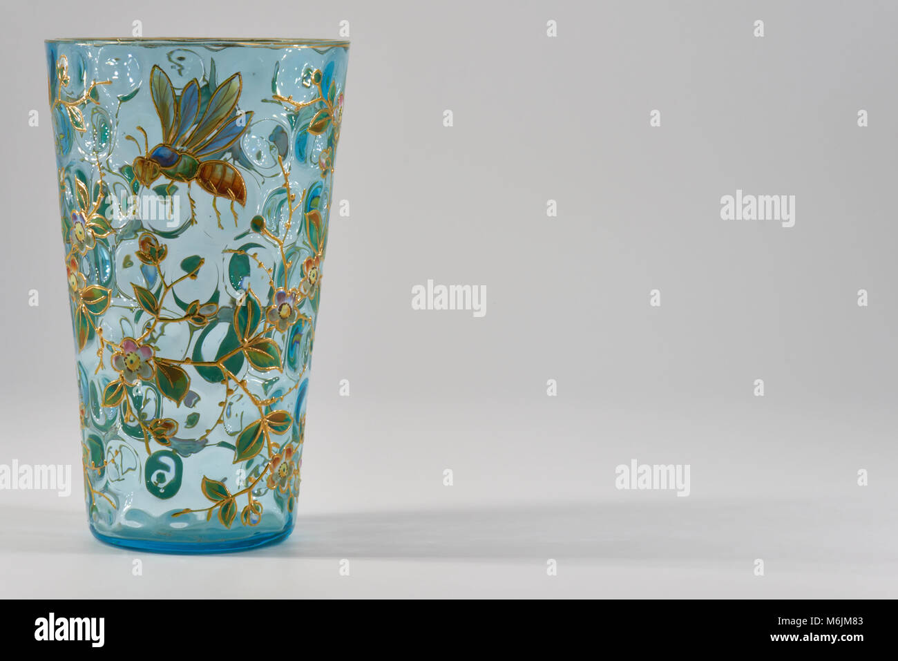 A 17th Century, Pale blue Glass Vase, embellished with an enamel of Flowers, leaves and Honey Bee's standing - Stock Image
