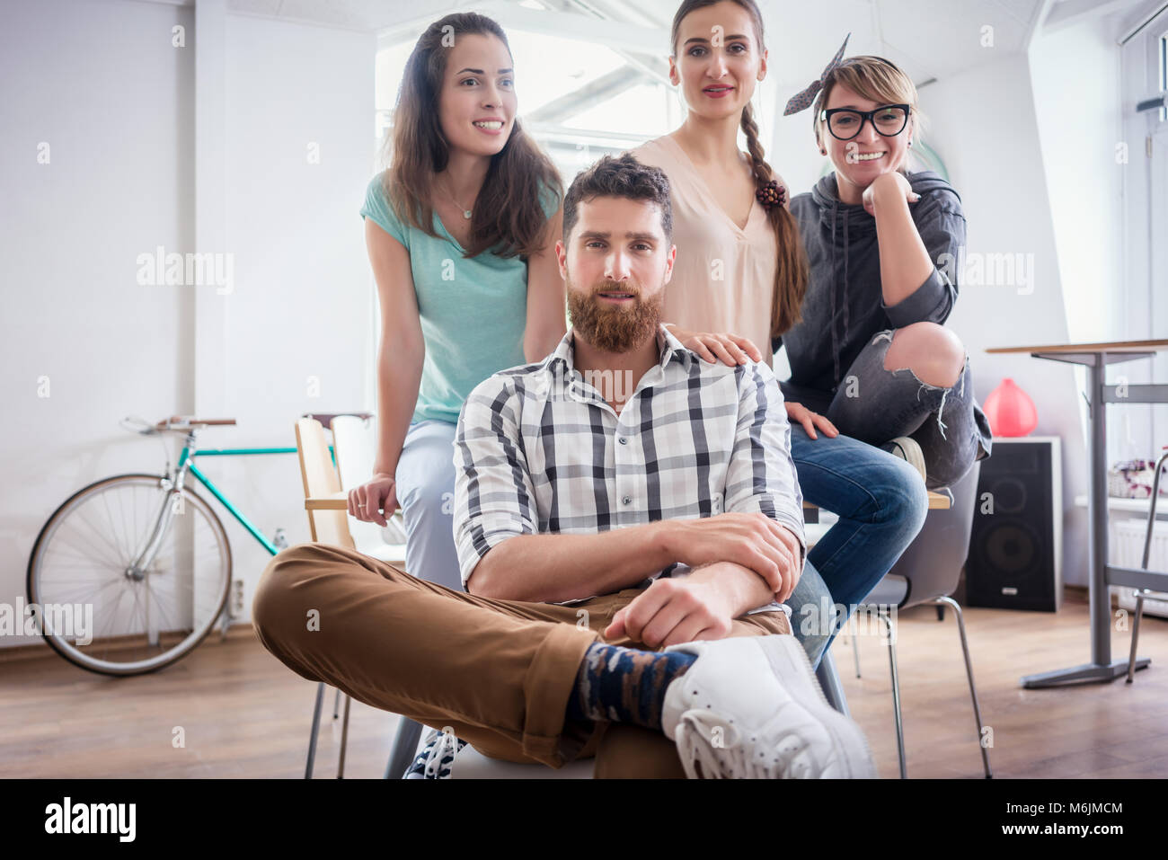 four co-workers wearing casual clothes during work in a modern hub - Stock Image
