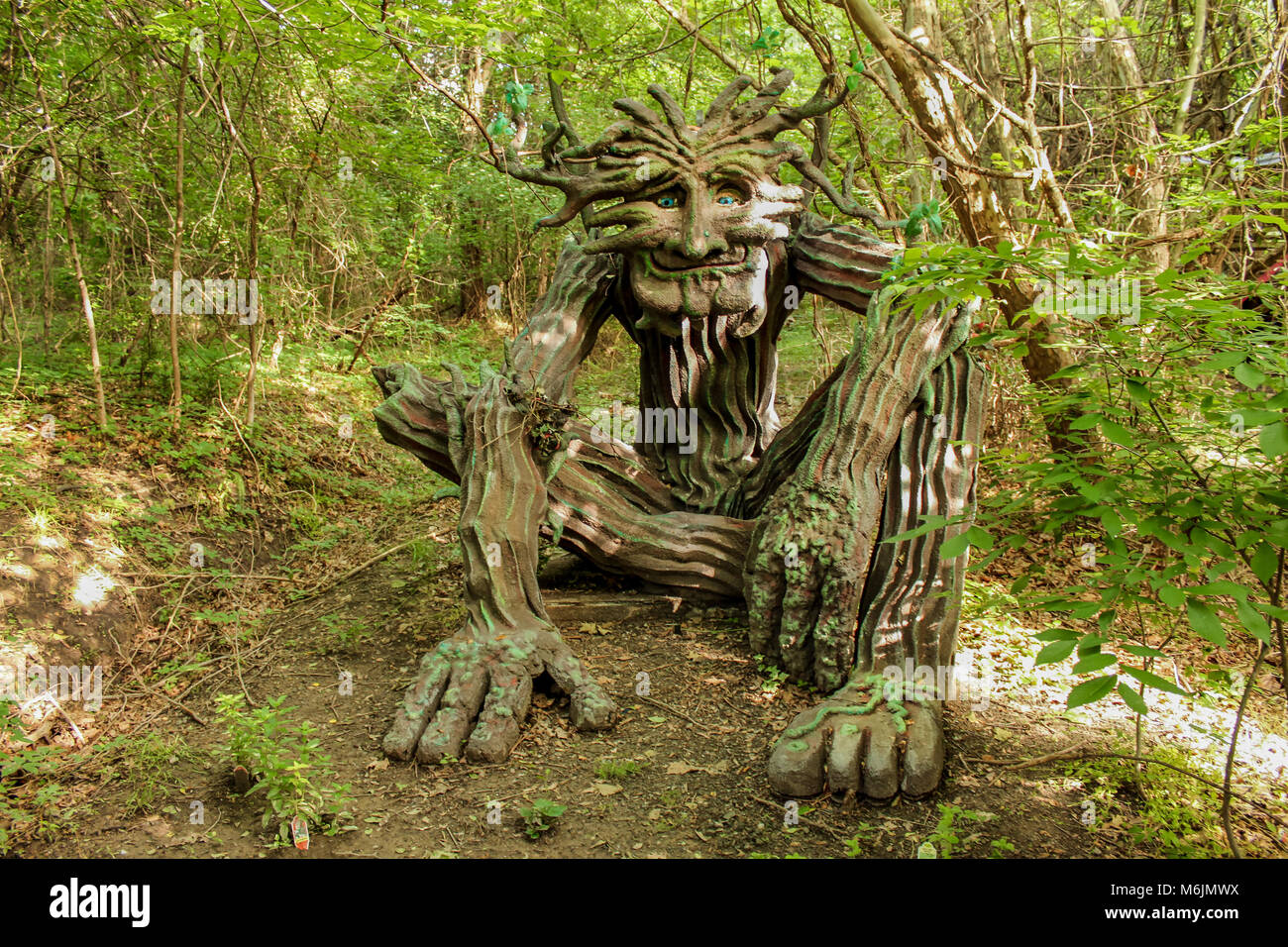 Woodland greenman sculpture setting in forest dappled with sun and shade at Renassiance Festival Muskogee Oklahoma Stock Photo