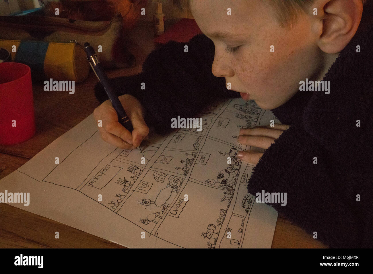 7-year old boy drawing at the breakfast table. Non-digital, non-screen, analogue entertainment. - Stock Image