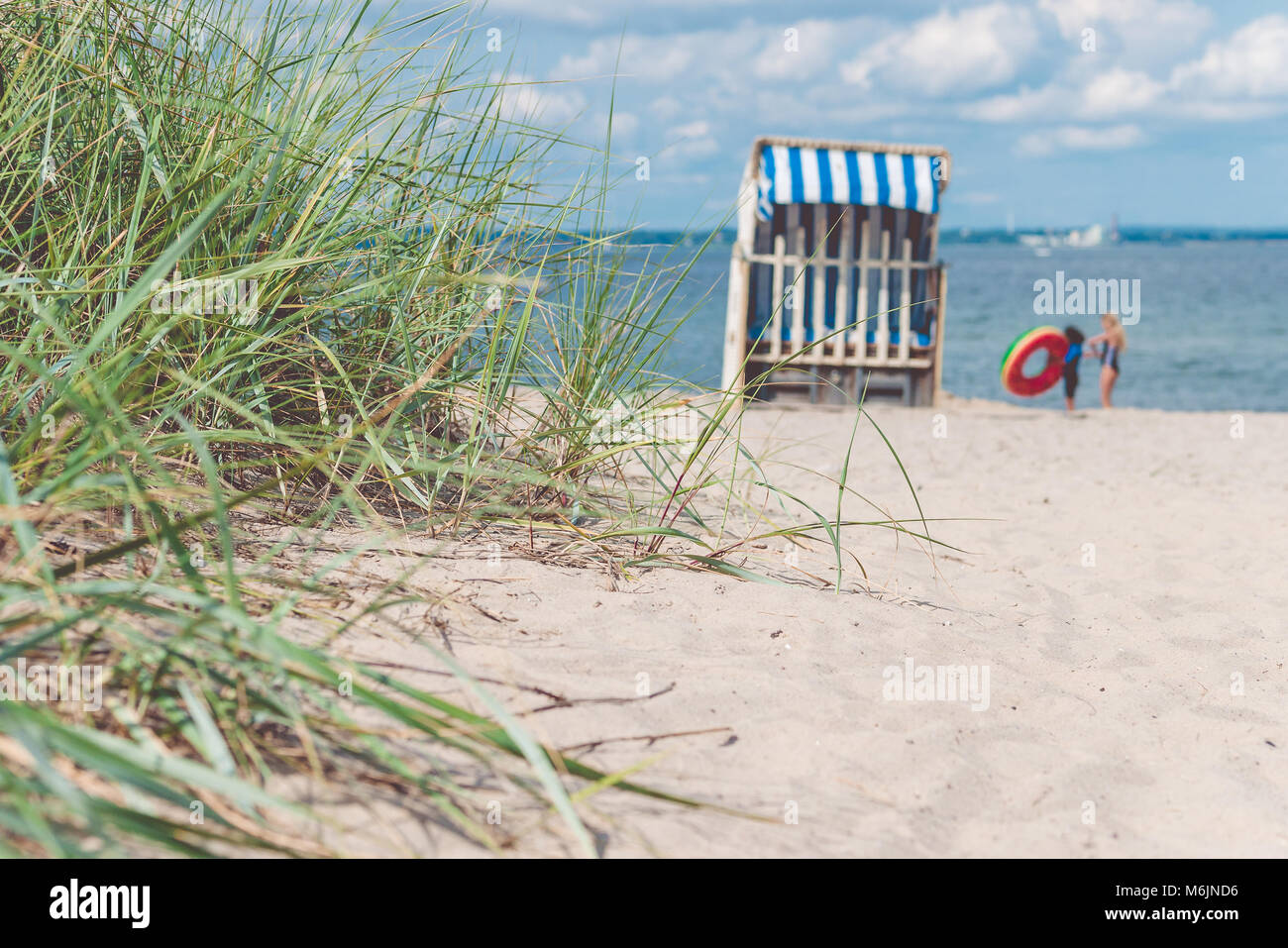 Sand dune with grass and blue colored roofed chairs on sandy beach and blurred kids in Background. Travemunde. Germany - Stock Image