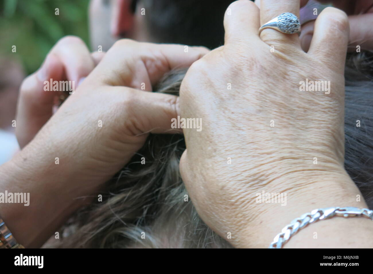 More than one pair of hands was needed to help unpin the bridesmaid's hair - Stock Image