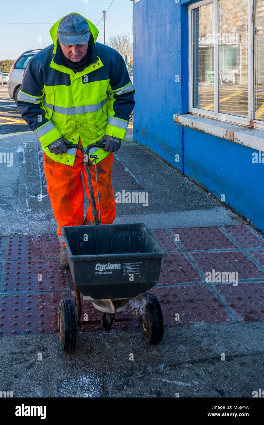 County Council worker gritting the pavement during Storm Emma in Schull, County Cork, Ireland. - Stock Image