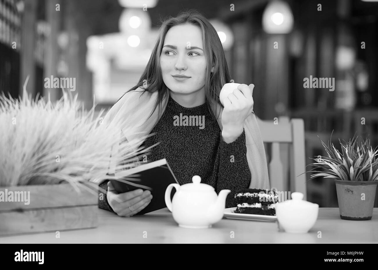 Girl in a cafe sitting and drinking tea - Stock Image