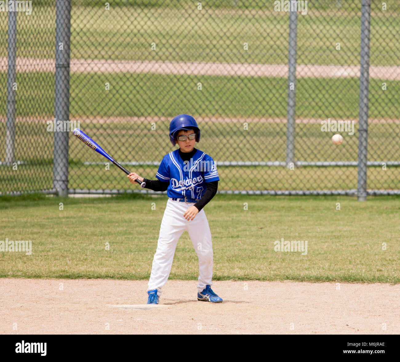 A young boy watches the ball go past him during a game of baseball in Cairns, Australia - Stock Image