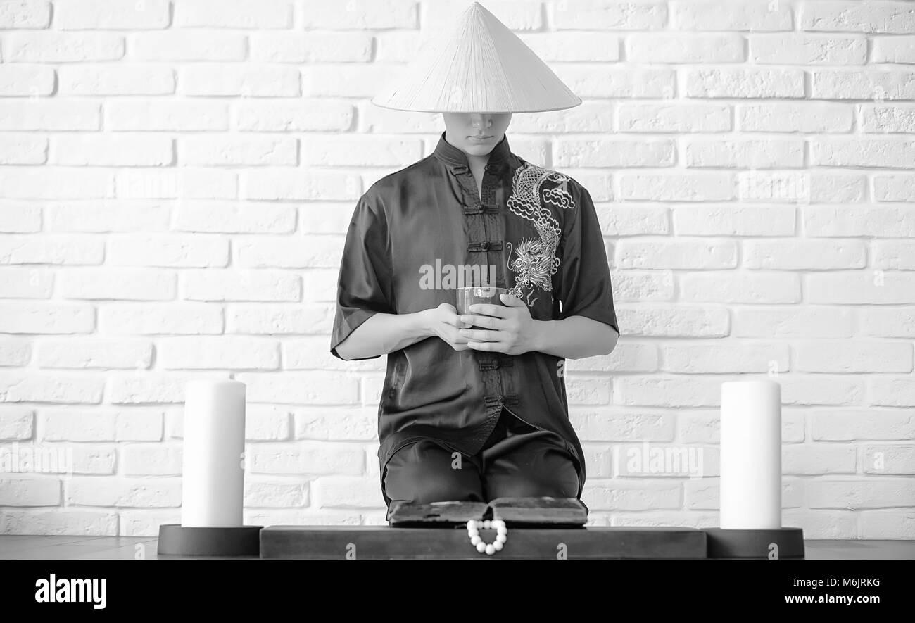 Asian novice on a white brick wall - Stock Image
