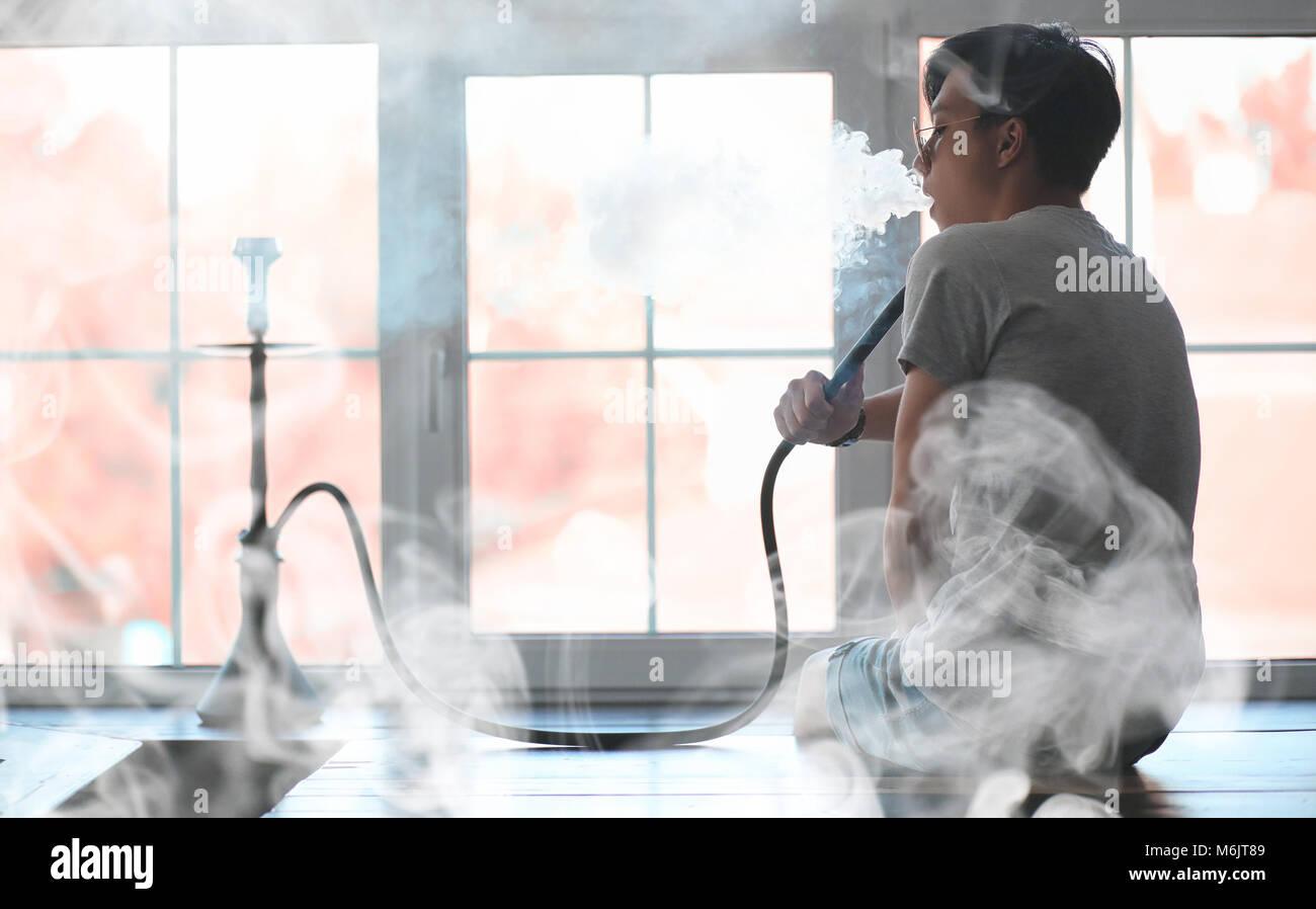 Man in sunglasses smoking a hookah - Stock Image