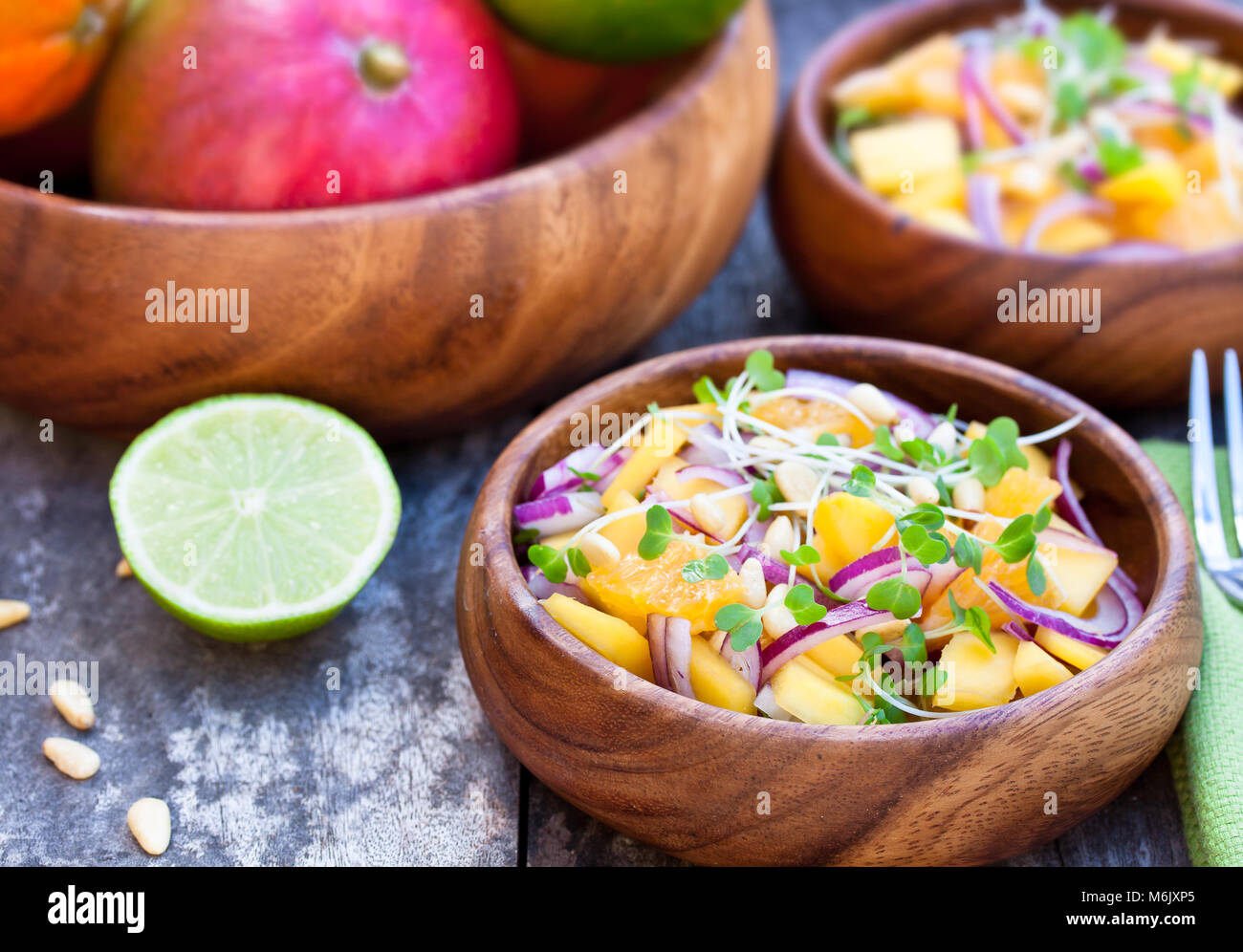 vegetarian  salad with mango oranges and red onion in the wooden plate - Stock Image