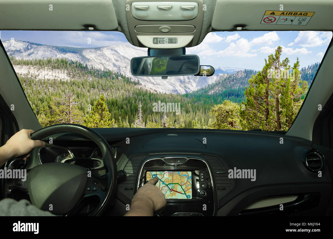 Driving a car while using the touch screen of a GPS navigation system in Yosemite National Park, California, USA - Stock Image