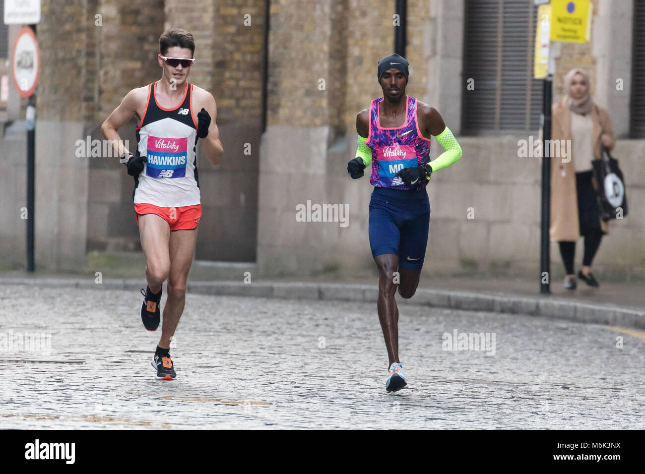 London, UK. 4th March 2018. Mo Farah and Callum Hawkins on cobbled streets in Wapping as they approaches the half - Stock Image