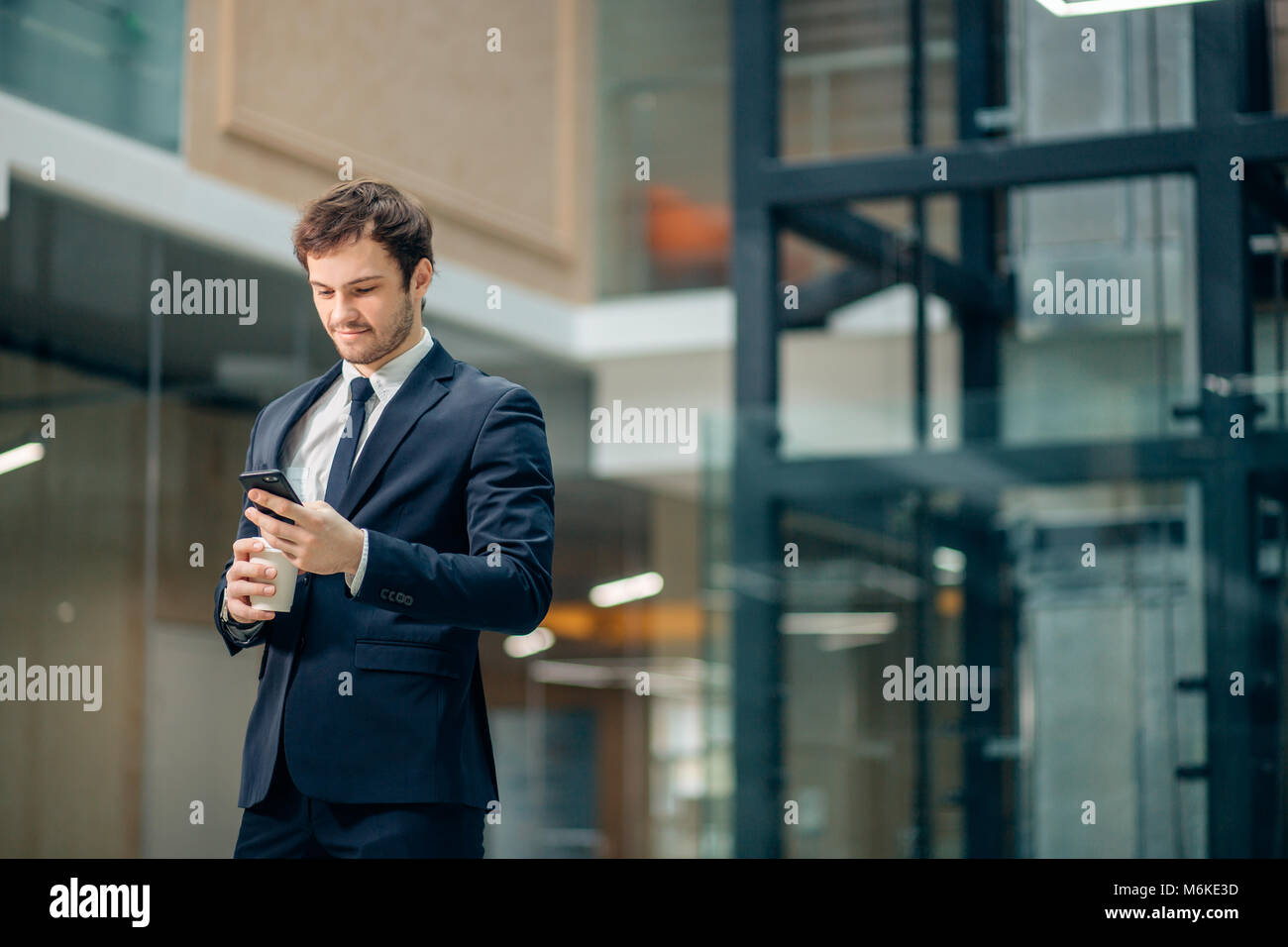 Businessman in black suit drinking takeaway coffee and use phone - Stock Image