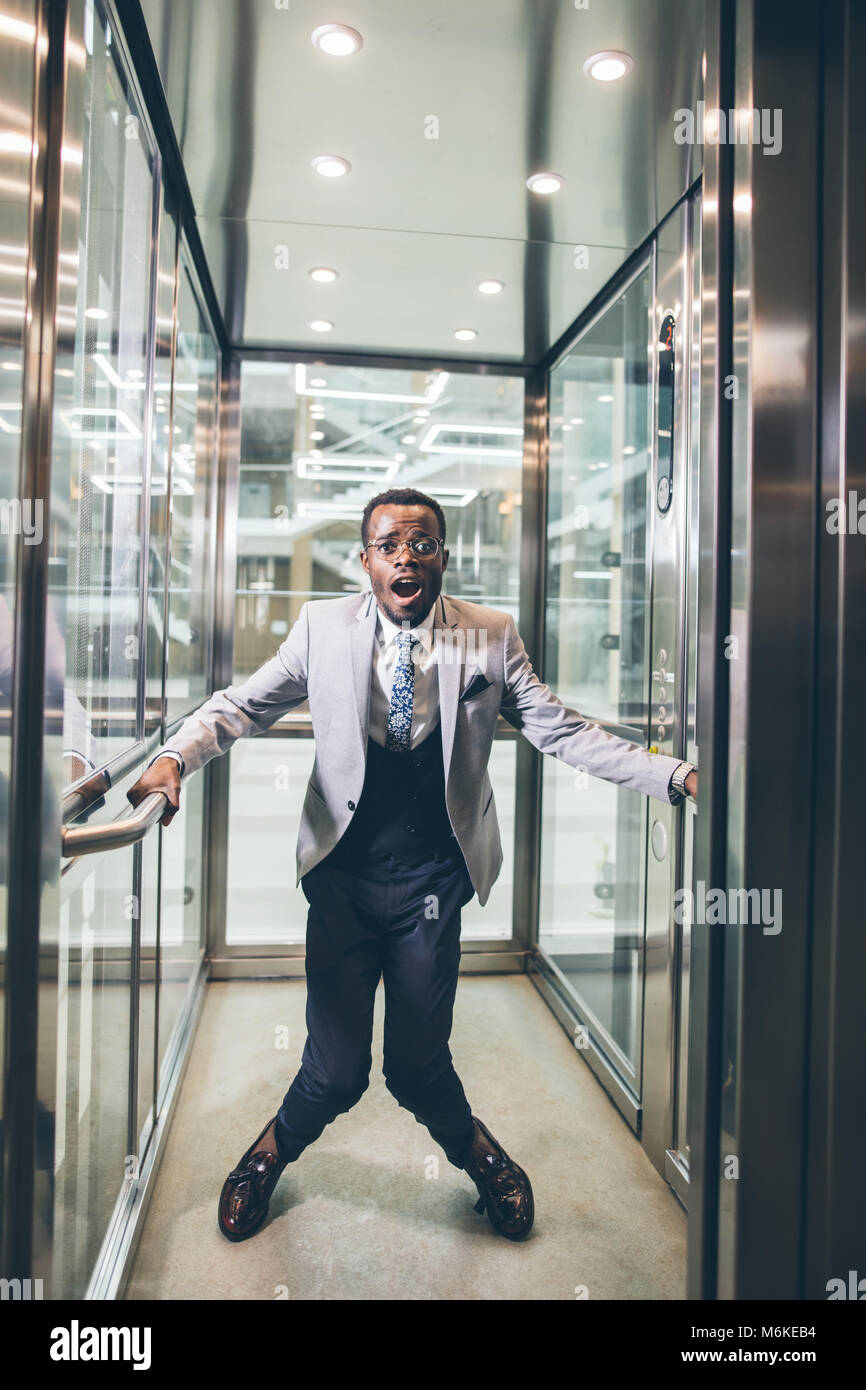 african Businessman screaming in elevator. fear claustrophobia concept - Stock Image