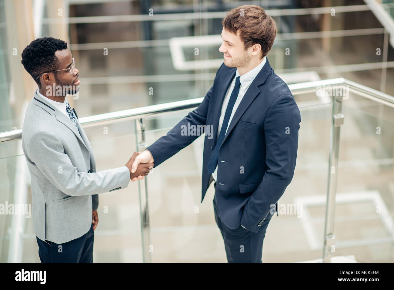 two multiracial businessmen handshaking in modern office for end of great deal - Stock Image