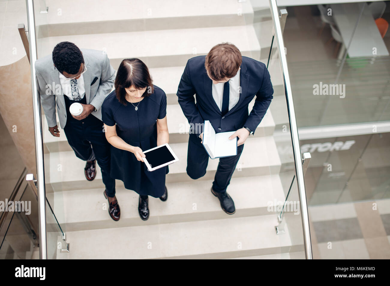 Three multiracial business people walking down on stairs with digital tablet - Stock Image